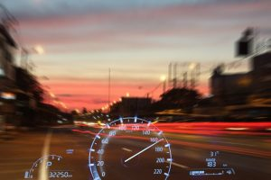 reckless driving by speeding - double exposure of road and speedometer